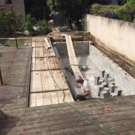 Daniel Spagnolo en train de monter les murs de la piscine.